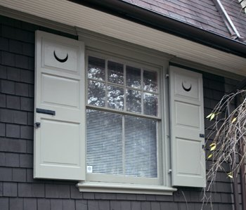 Panels and crescent moons give a distinctive look to these wooden shutters painted white.