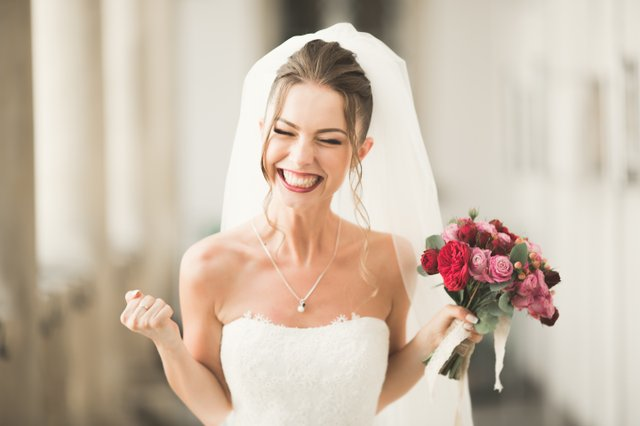 Luxury wedding bride, girl posing and smiling with bouquet